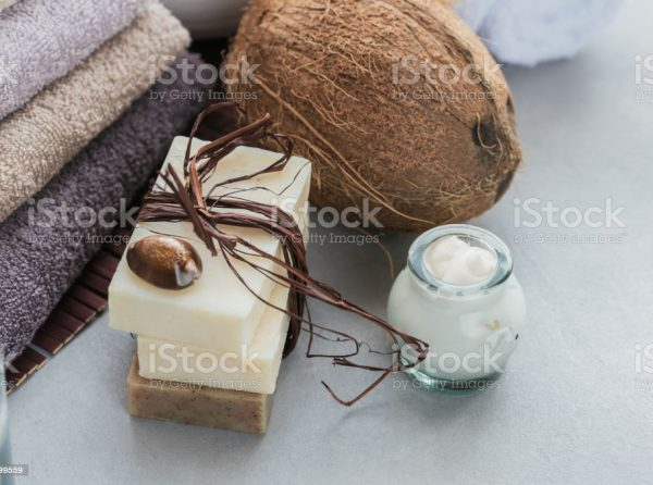 Organic cosmetics with coconut oil, sea salt, towels and handmade soap on grey background. Natural ingredients for homemade facial and body mask or scrub. Healthy skin care. SPA concept.